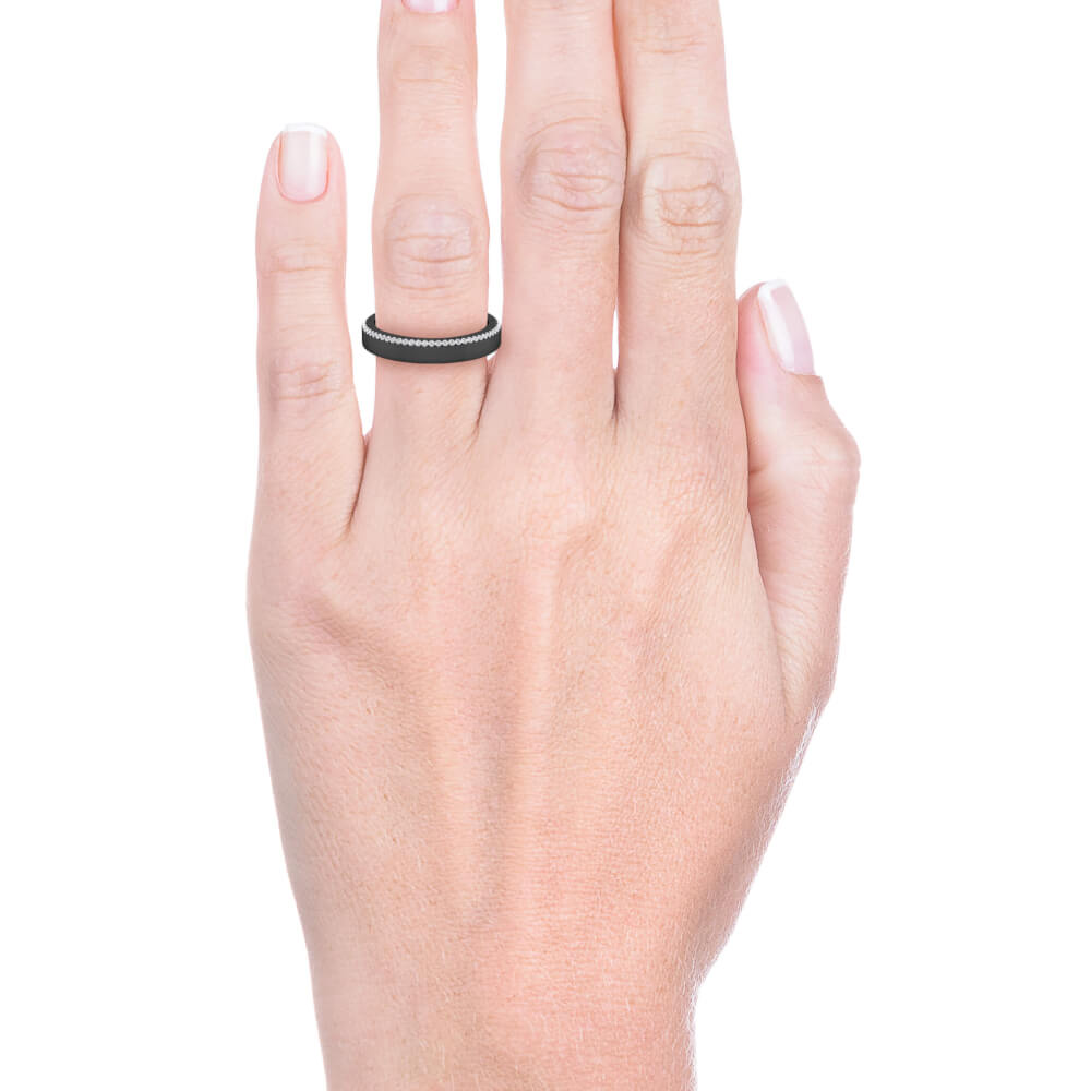 mano con alianza de boda de oro negro y diamantes