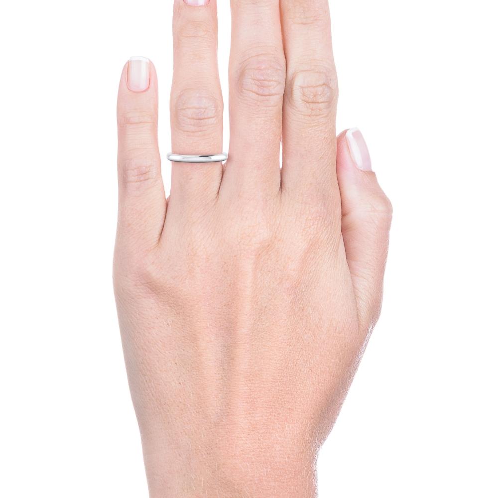 Mano con alianza de boda clásica para mujer de oro blanco media caña 18 kilates