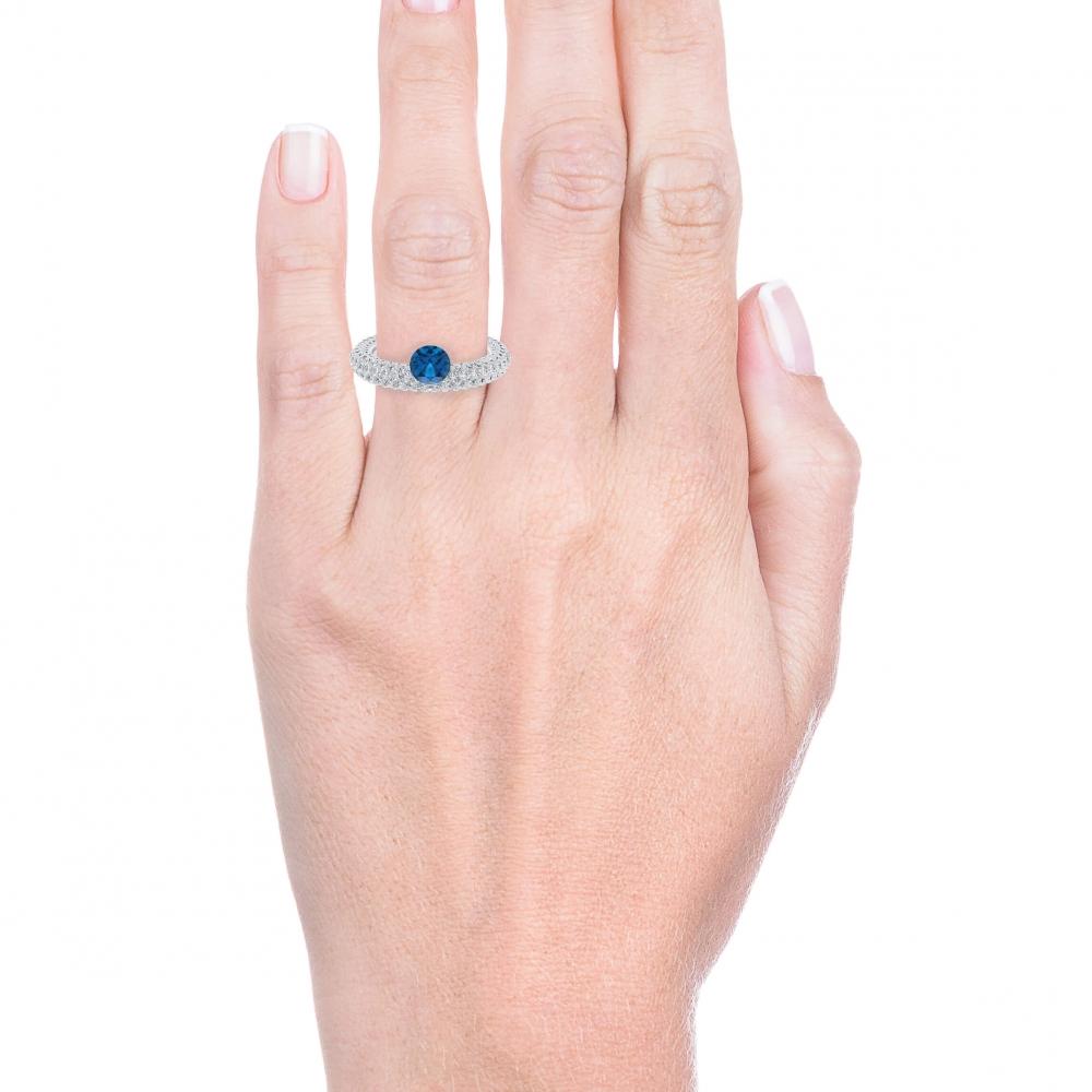 mano con Anillo de compromiso de oro blanco 143 diamantes y Zafiro azul