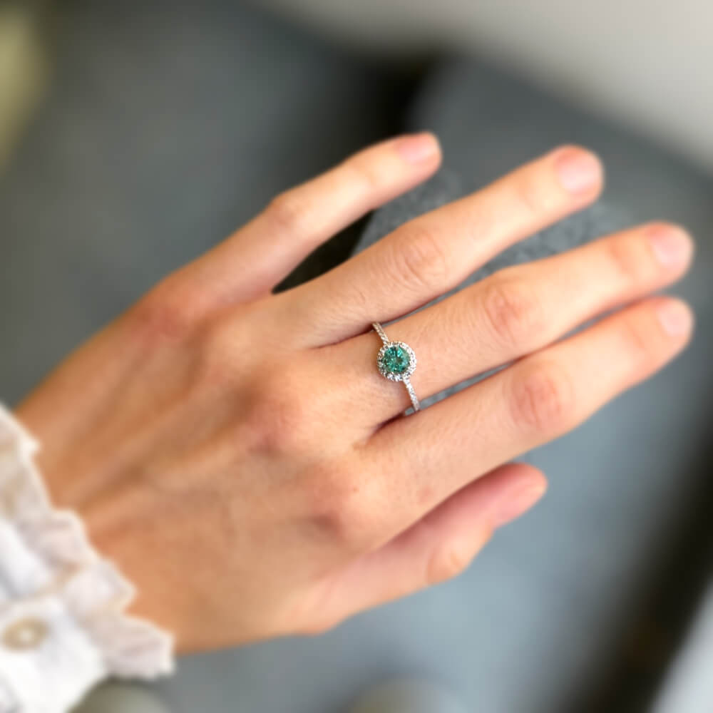 Halo diamond engagement ring with emerald