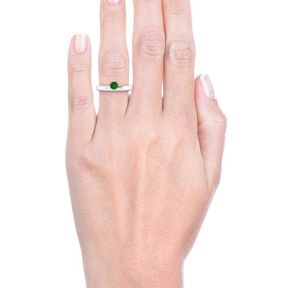 mano con alianza de compromiso de oro blanco y esmeralda
