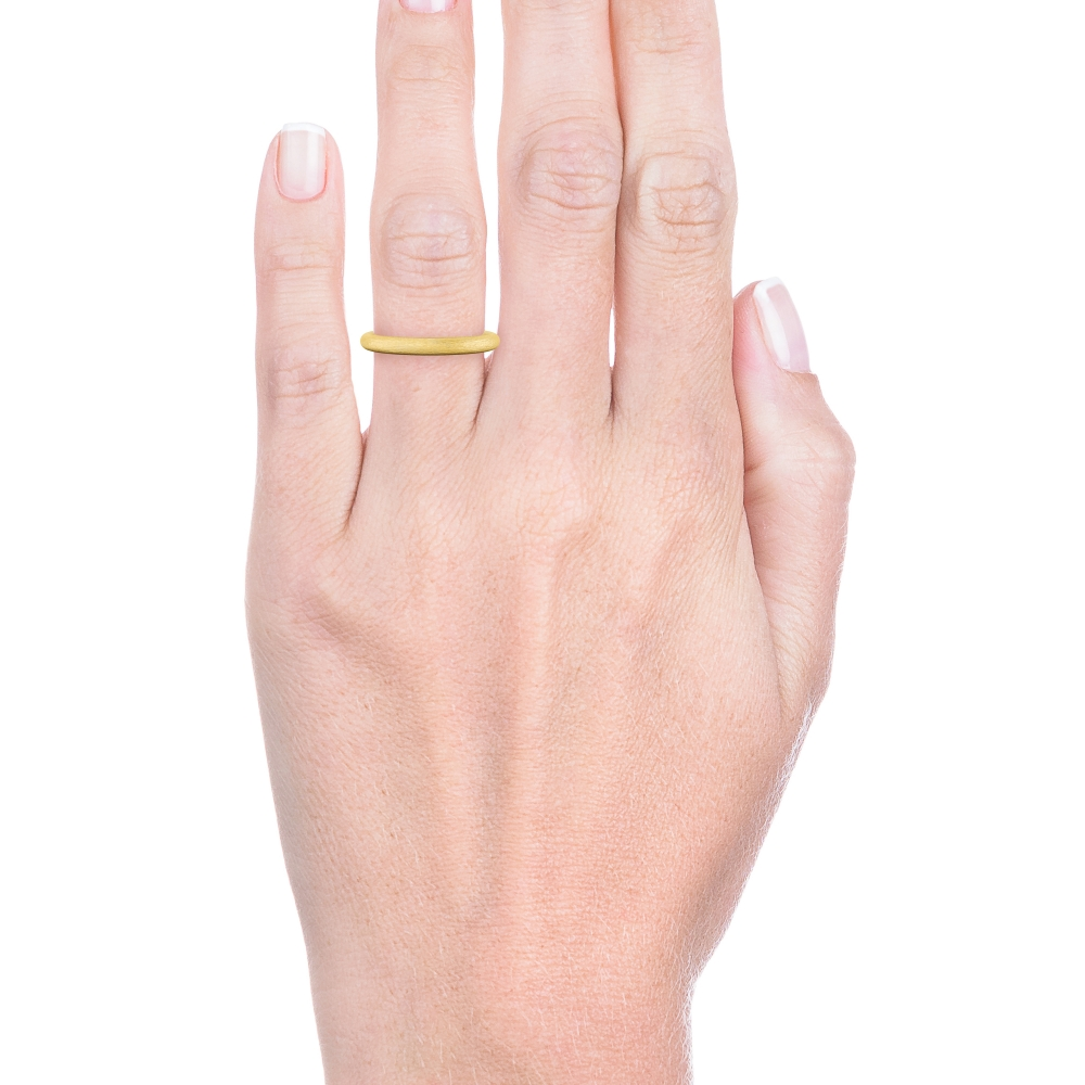 mano con alianza de boda redonda en oro amarillo